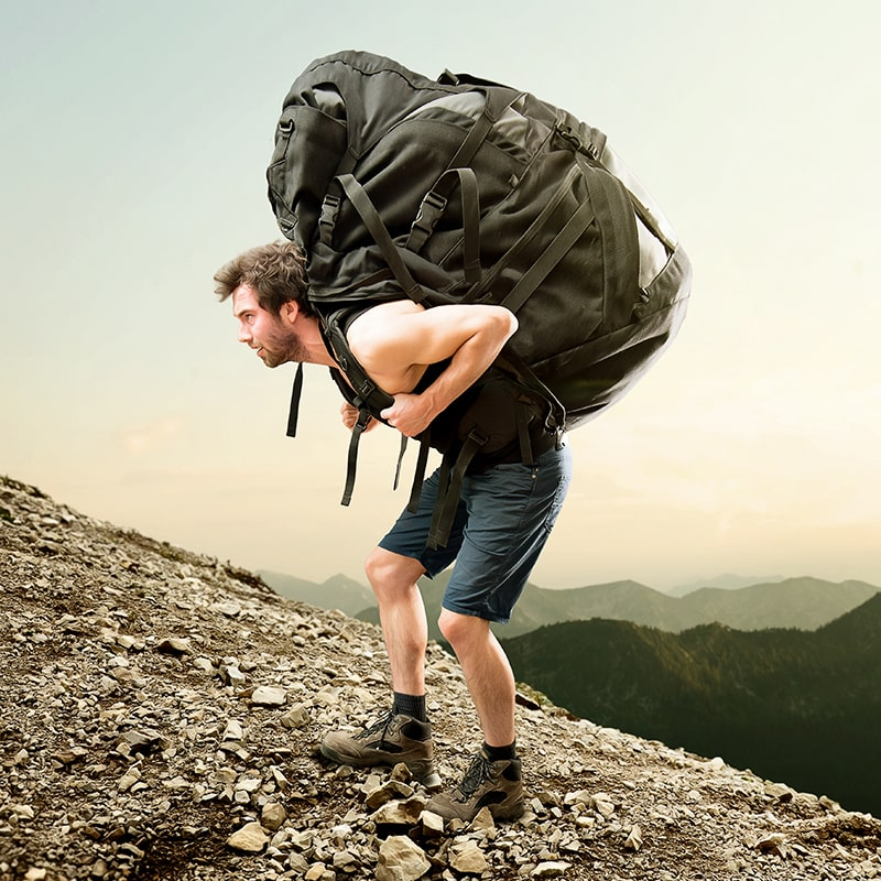 How Heavy Should Your Hiking Backpack Be for Hiking - Backpacker with Heavy Backpack