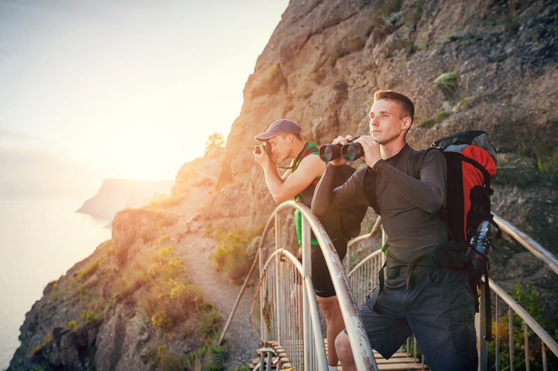 Find a Hiking Partner - Two Guys Standing on a Bridge Looking through Binoculars and Photographing Nature