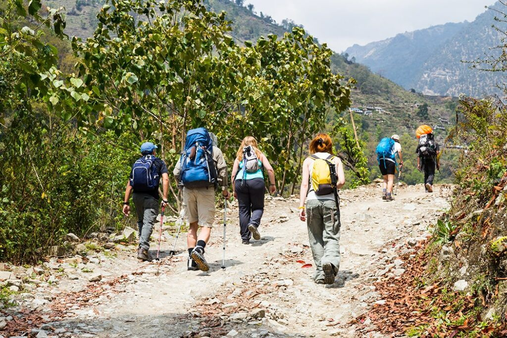 Hiking Backpack Recommendations - Group of People Trekking on a Dirt Road in Nepal