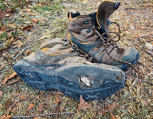 The Best Hiking Boots - Pair of Old Hiking Boots near a Creek